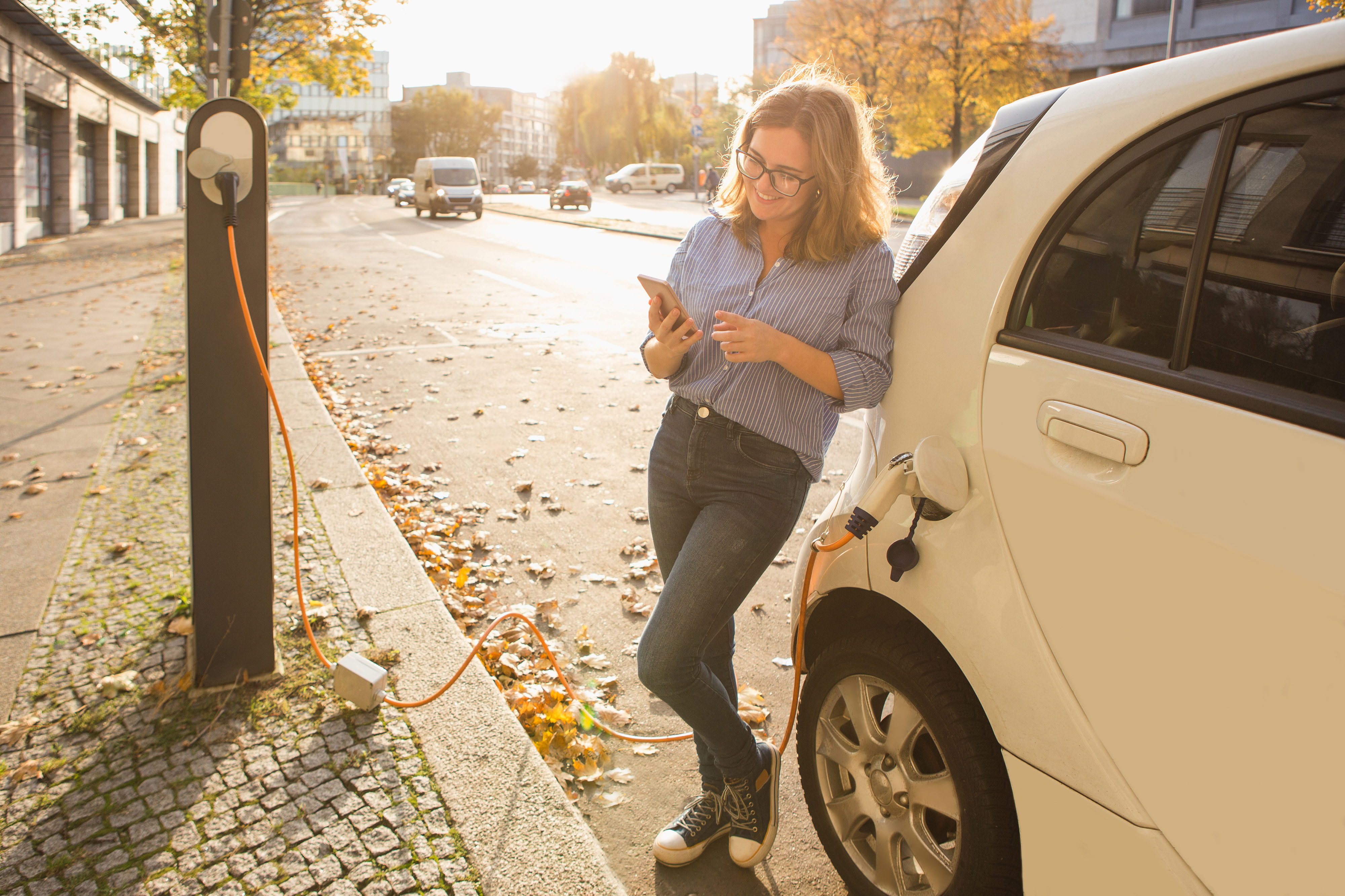 lady leaning on charging car on phone