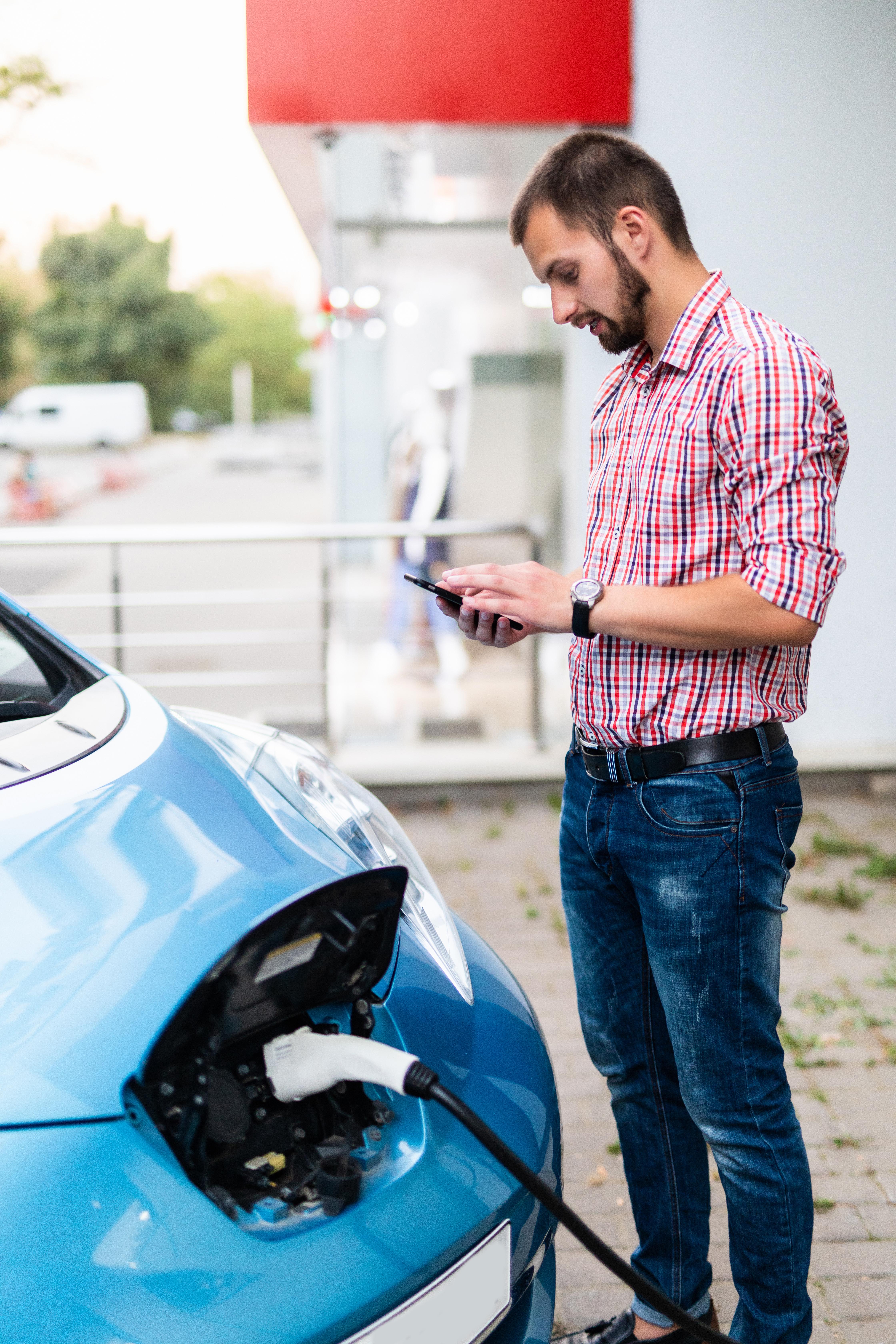 man checking phone charging car-1